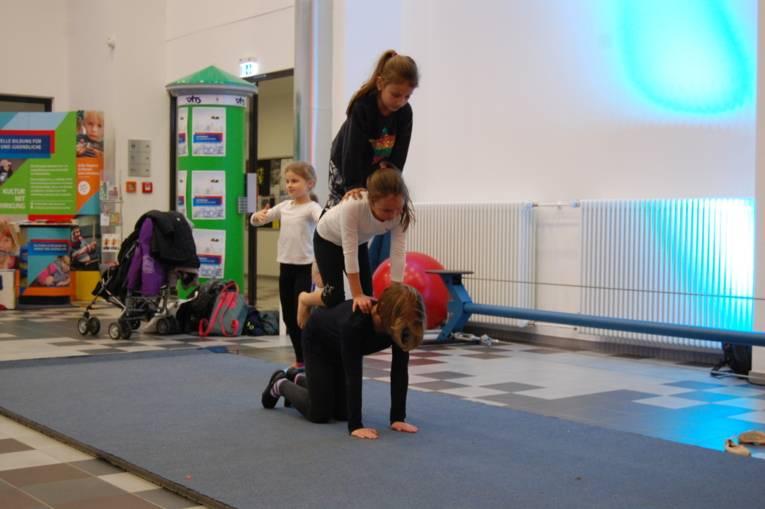 Mehrere Mädchen turnen eine akrobatische Figur.