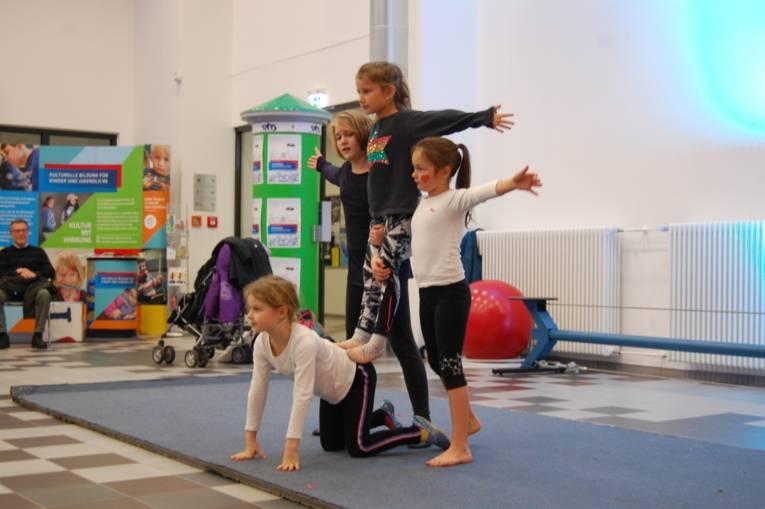 Mehrere Mädchen bilden eine kleine Pyramide.