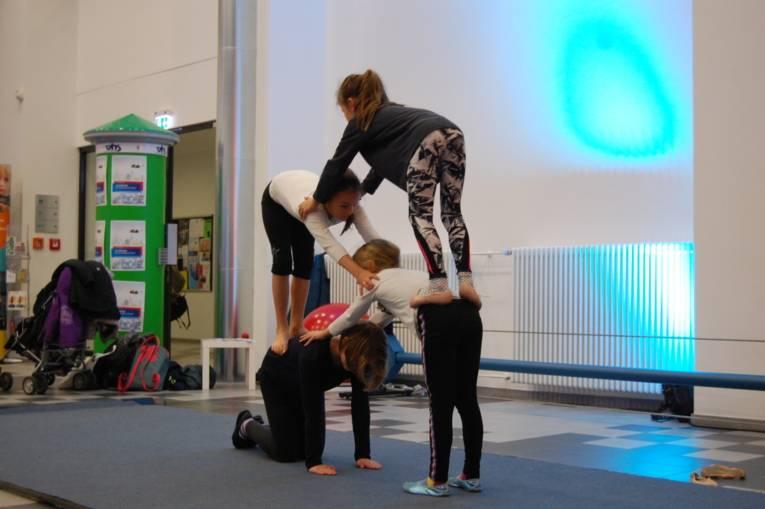 Mehrere Mädchen turnen eine große Pyramide.