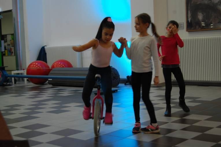 Ein Kind fährt Einrad und wird von einem anderen Kind gestützt.
