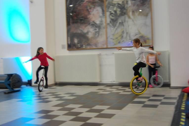 Zwei Kinder fahren auf Einrädern im Kreis herum.