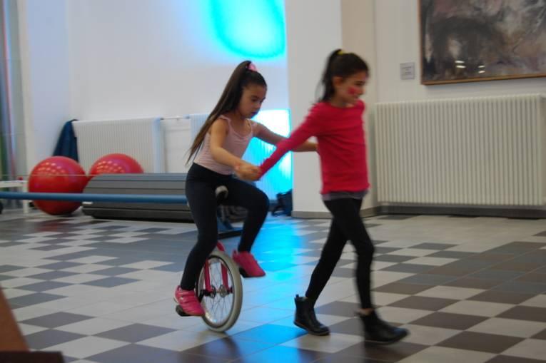 """Ein Kind fährt Einrad, ein anderes Kind läuft vorne weg. Das Kunststück heißt """"Die Kutsche""""."""