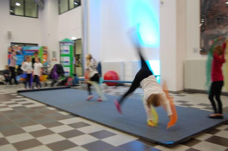 Zwei Mädchen machen Akrobatik auf einer blauen Matte.