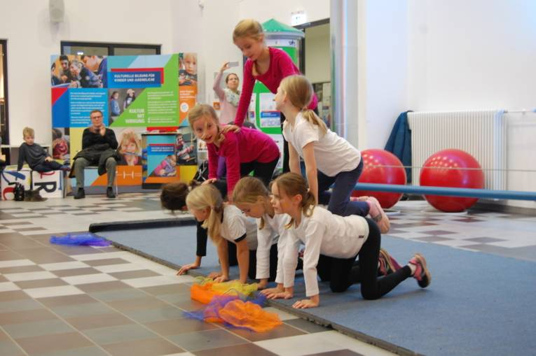"""Eine Gruppe von Kindern turnt eine """"Pyramide""""."""