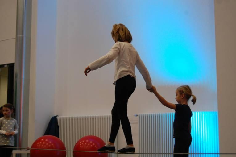 Ein Mädchen läuft auf einem Hochseil, ein anderes stützt sie dabei.