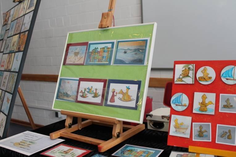 Auf einer Staffelei steht ein Bilderrahmen, auf dem verschiedene Postkarten befestigt sind. Auf den Karten sind kleine Figuren zu sehen.
