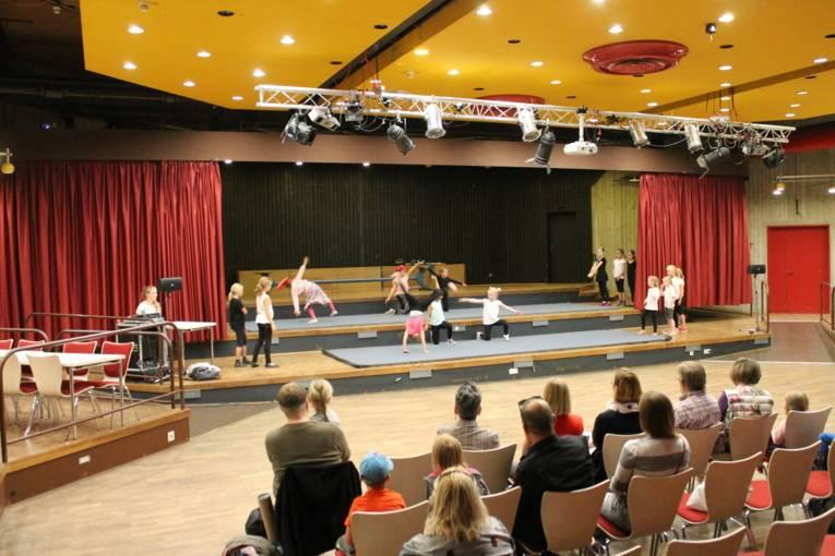 Man sieht Kinder, die auf einer Bühne akrobatische Kunststücke machen. Im Vordergrund sitzt das Publikum und schaut gebannt zu.