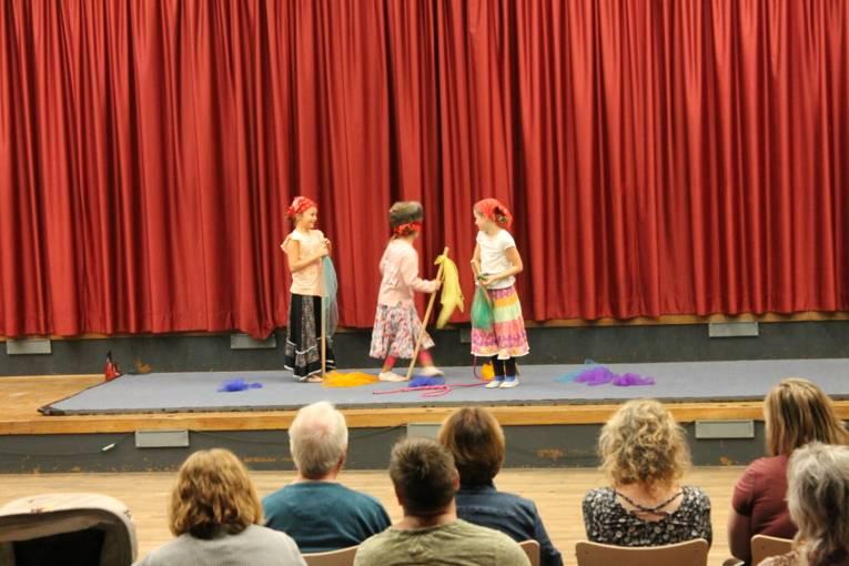 Auf einer Bühne stehen drei Mädchen in Putzfrauen-Kostümen und spielen eine Clownsnummer.
