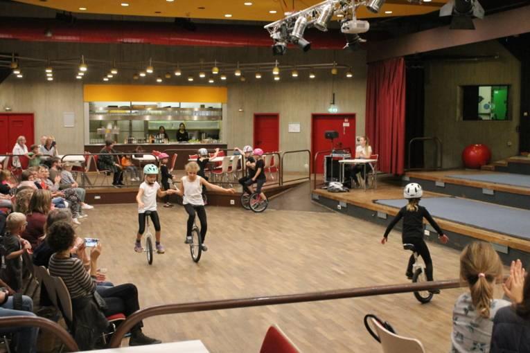 Mehrere Mädchen fahren in der Mitte des Saales mit ihren Einrädern. Links sitzt das Publikum und klatsch begeistert Beifall.