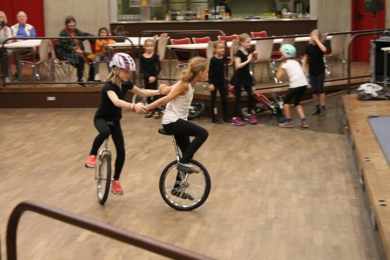 Zwei Mädchen halten sich beim Einradfahren an den Händen. Sie fahren gemeinsam einen Kreis.