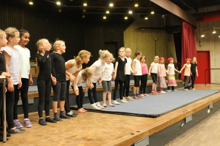 Alle Kinder vom Kinderzirkus stehen auf der Bühne und verbeugen sich nach dem gelungenen Auftritt.