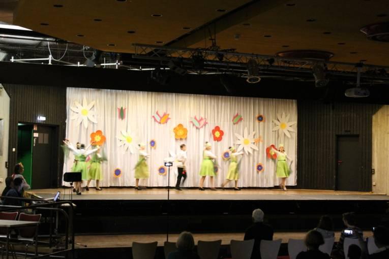 Die Tänzerinnen und Tänzer der Tanzgruppe Legende führen auf der Bühnen einen Tanz vor. Im Hintergrund hängen große Blüten an der Wand.