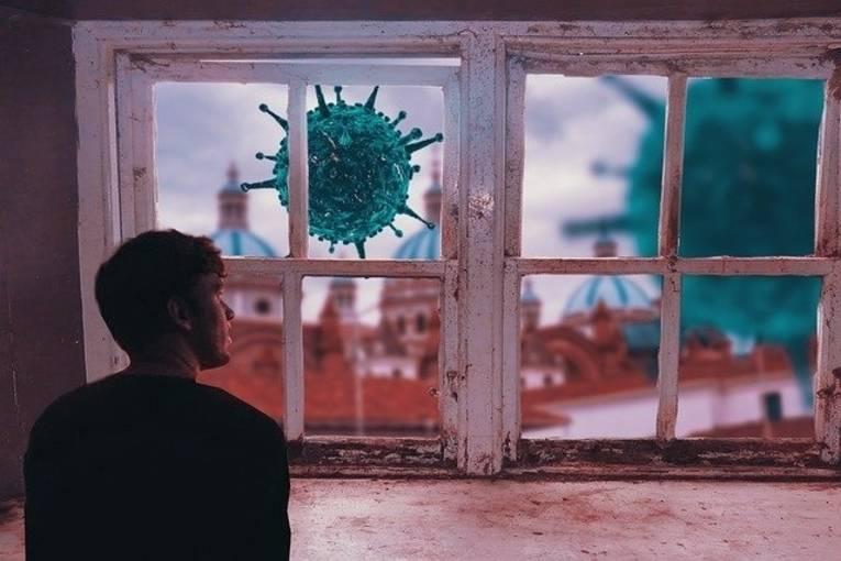Ein junger Mann sitzt an einem geschlossenen Fenster und sieht hinaus. Dort schwebt ein riesiges Virus-Molekül.