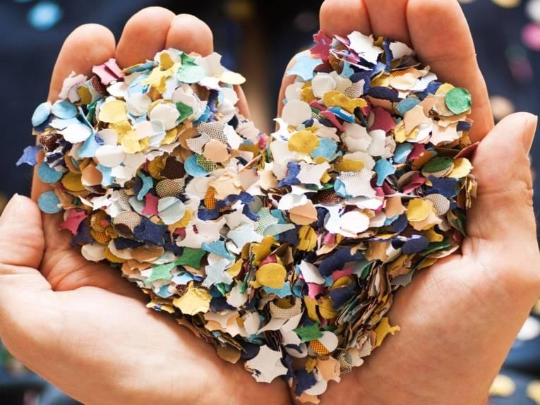 In ein in Händen gehaltenes Herz aus bunten Konfetti