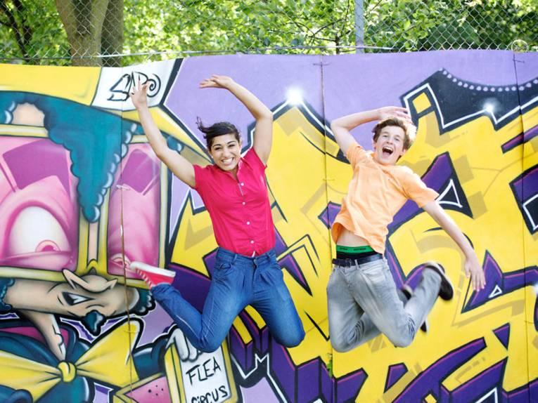 Zwei junge Leute vor einer Graffiti-Wand