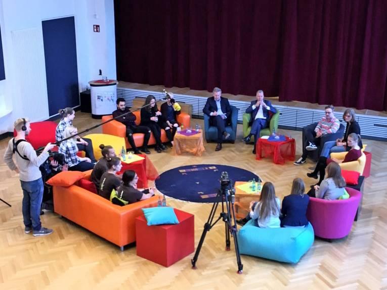 Eine Diskussionsveranstaltung, bei der die Teilnehmenden im Kreis sitzen, wird im Europasaal des Haus der Jugend aufgezeichnet.