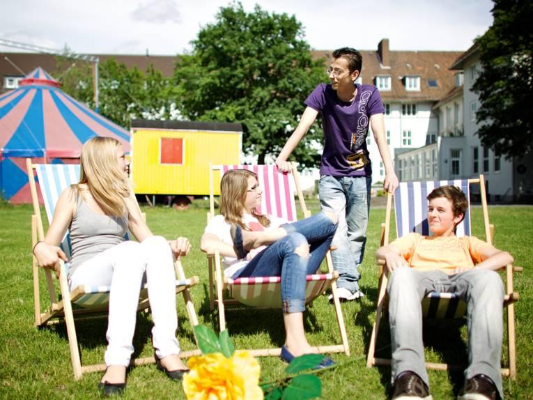 Vier Jugendliche vor dem Haus der Jugend - drei in Liegestühlen und ein junger Mann im Gespräch dahinter