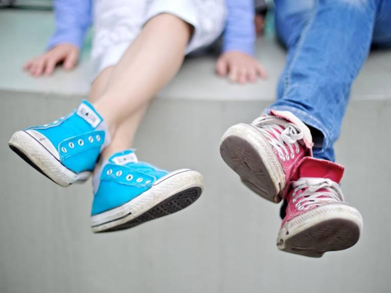 Nahaufnahme von hellblauen und rosa Turnschuhen von zwei Jugendlichen