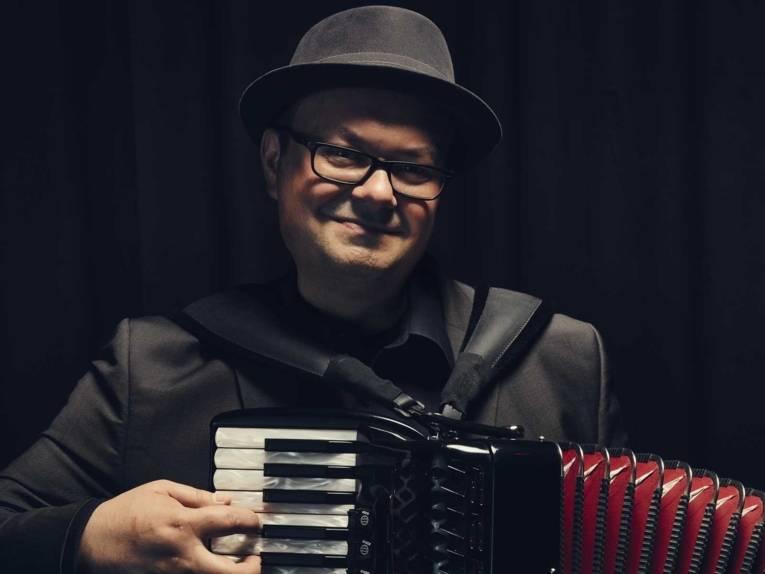Mann mit Hut und Brille spielt Akkordeon.