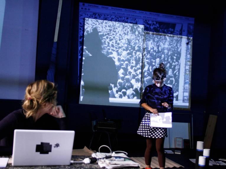 Eine Frau am Computer, eine andere vor einer Leinwand im dunklen Raum.