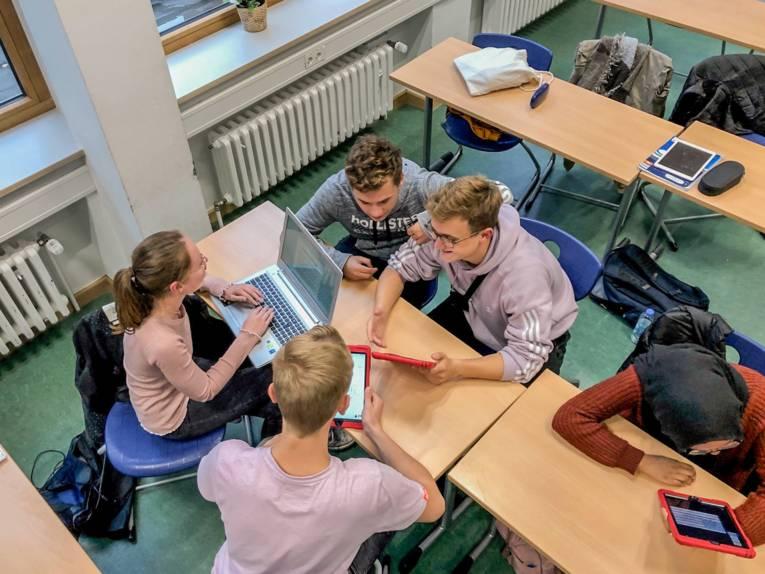 Fünf junge Leute sitzen an Schultischen und arbeiten mit Tablets und einem Laptop