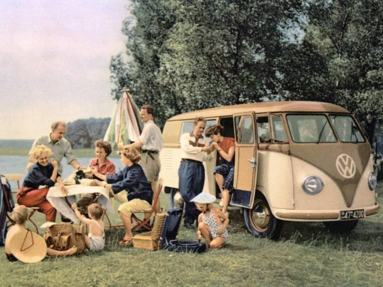 """Picknickszene im Grünen mit einem VW-Bus, Farbdruck nach einem Foto aus einem Werbeblatt """"VW-Achtsitzer"""", (um 1954)"""