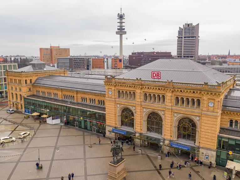 Die linke Seite der Front des Hauptbahnhofs Hannover mit dem Ernst-August-Denkmal davor von oben gesehen