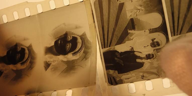 Das Foto zeigt drei Bilder eines 35-Millimeter-Filmnegativs. Rechts unten sieht man einen Daumen der Hand, die den Streifen bei der Restaurierung hält.