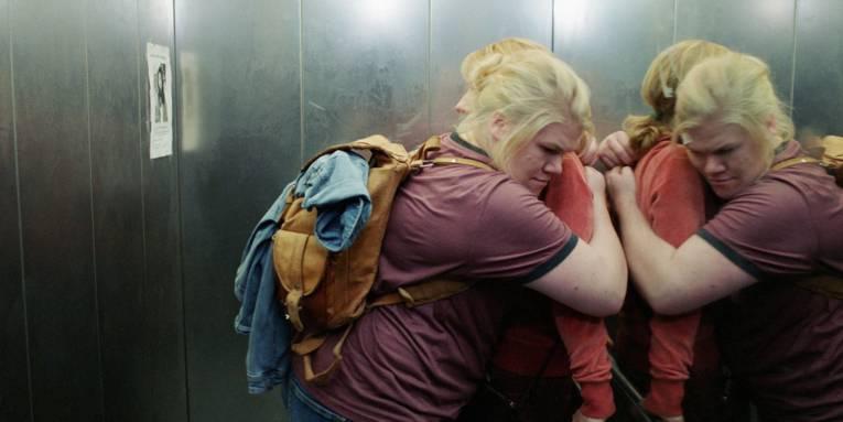 Zu sehen sind zwei Personen die sich in einem Fahrstuhl umarmen.