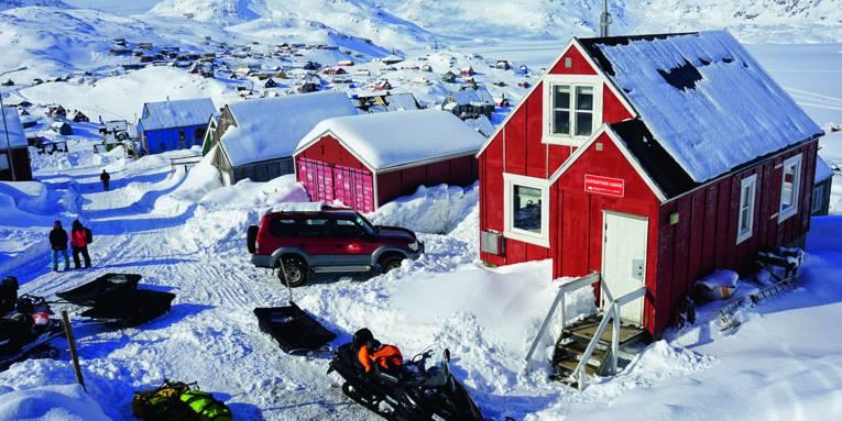 Auf dem Foto ist eine grönländische Siedlung mit viel Schnee zu sehen. Auf der rechten Bildseite steht The Red House in einem warmen Rotton