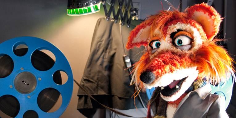 Eine Fuchs-Stoffpuppe mit einer Filmrolle.