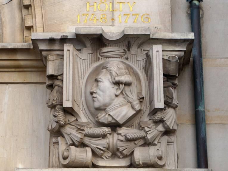 Ein Porträtmedaillon von Ludwig Hölty an der Gartenseite des Neuen Rathauses, oberhalb des Medaillons stehen der Nachname und die Lebensdaten