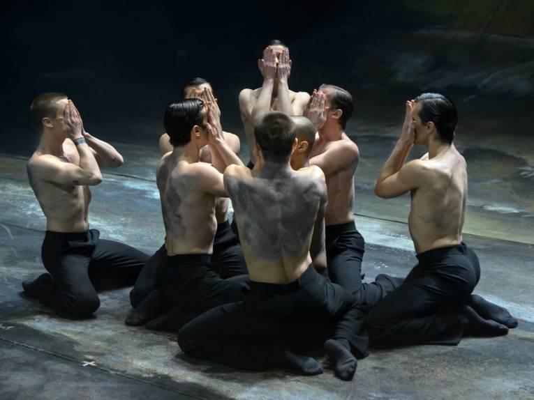 Sieben Männer knien im Kreis und halten ihre Hände vors Gesicht