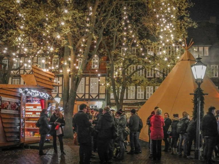 Besucherinnen und Besucher des Weihnachtsmarkt unterhalten sich vor der Kulisse des finnischen Dorfes mit Tipi und Holzhütten