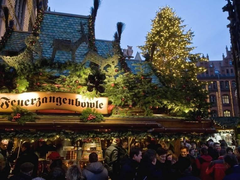 """Ein weihnachtlich geschmückter Stand mit der beleuchteten Aufschrift """"Feuerzangenbowle"""" auf dem Marktplatz neben der Marktkirche"""