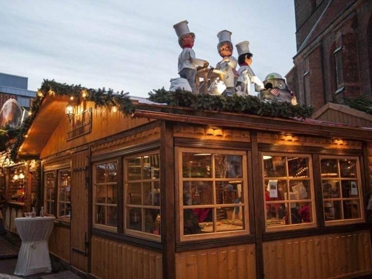 Drei Figuren auf einem Holzdach weisen den Weg zur Weihnachtsbackstube