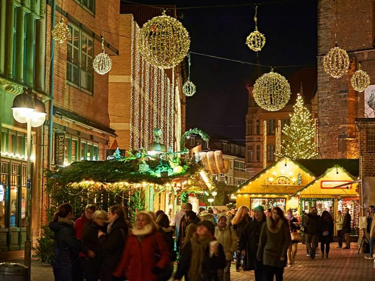 Besucherinnen und Besucher des Weihnachtsmarktes an der Marktkirche schlendern zwischen den mit Tannen verzierten Ständen und genießen die stimmungsvolle Beleuchtung