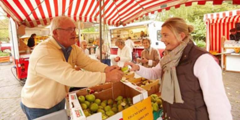 Markthändler gibt Kundin ein Apfelschnitz zum Probieren