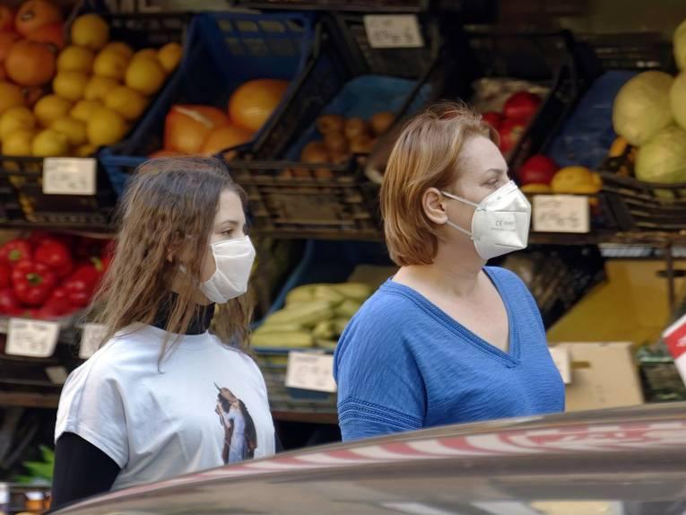 Zwei Frauen mit Mund-Nasen-Schutz gehen an einem Marktstand vorbei.
