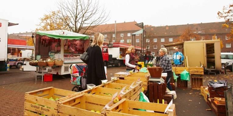 Zwei Kundinnen an einem Marktstand mit frischen Äpfeln