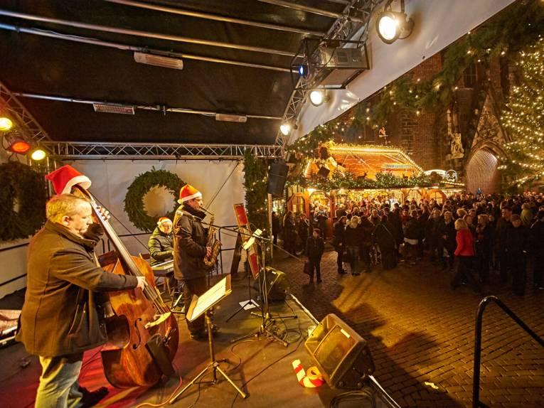Drei Musiker (Bass, Saxofon und Keyboard) spielen mit Weihnachtsmützen vor Publikum auf einer Bühne an der Marktkirche