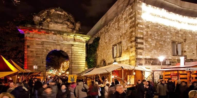 In der vorweihnachtlichen Dunkelheit sorgen der angestrahlte Torbogen und die Mauer des Historischen Museums für eine stimmungsvolle Kulisse der rundherum aufgebauten Marktstände, die von zahlreichen Besucherinnen und Besuchern frequentiert sind.