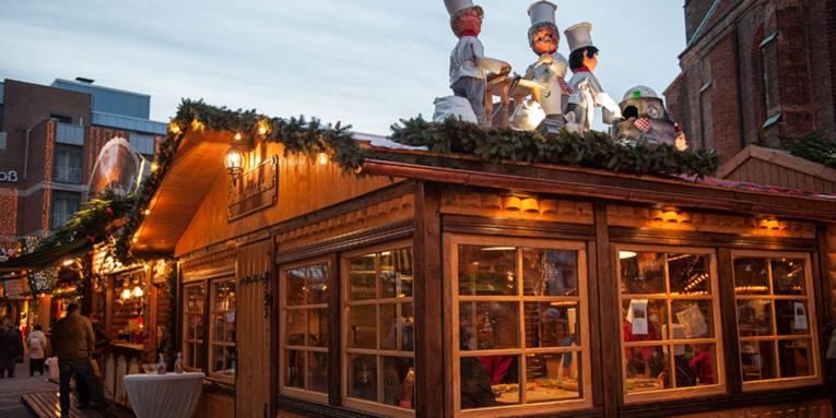 Auf dem Dach einer weihnachtlich geschmückten Holzhütte stehen Puppen in Bäckerkleidung; innen sind Kinder an einem großen Tisch damit beschäftigt, Weihnachtskekse auszustechen.