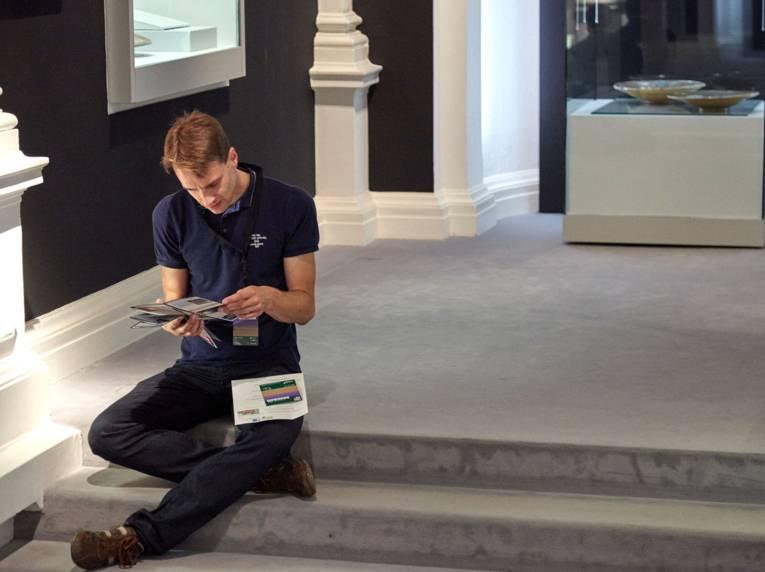 Rundgang im Museum, Mann sitzend studiert einen Flyer.
