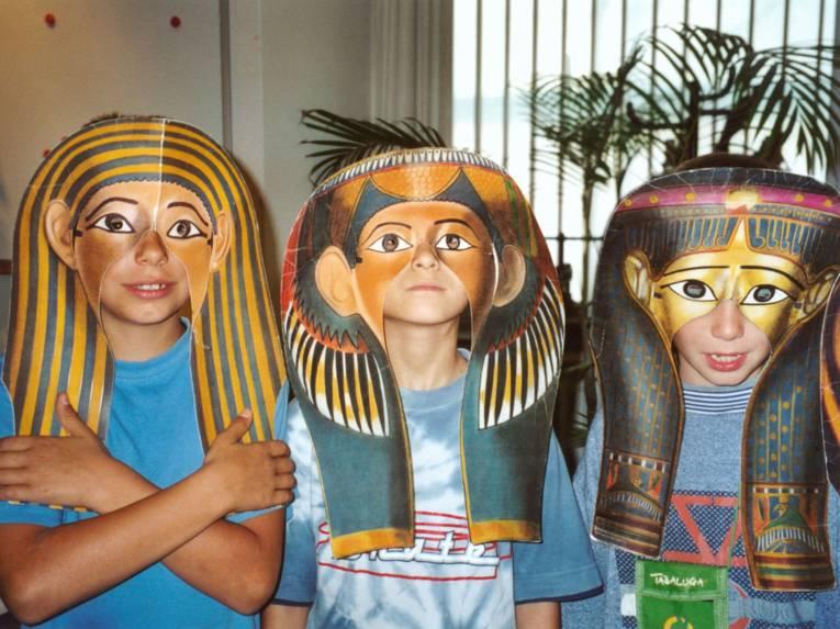 Drei Kinder hinter ägyptischen Masken.