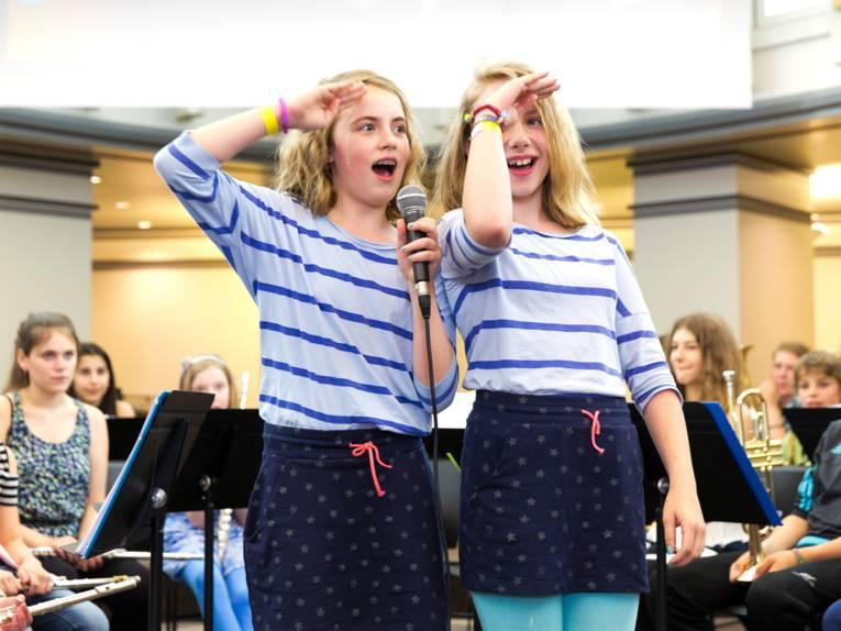 Anmoderation der Bläserklasse IGS Roderbruch: Zwei Schülerinnen performen vor dem versammelten Orchester auf der Bühne