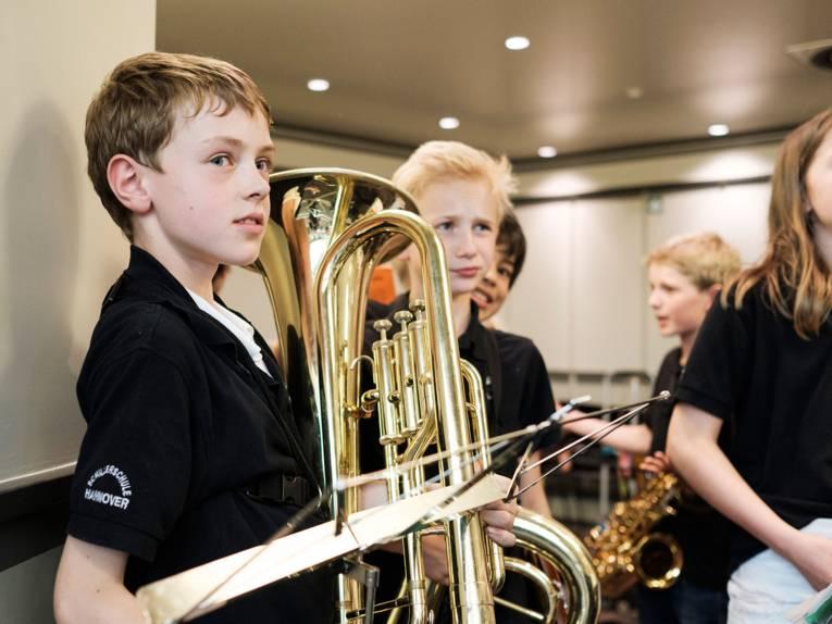 Vier Schüler der Bläserklasse Schillerschule mit Instrumenten vor ihrem Auftritt