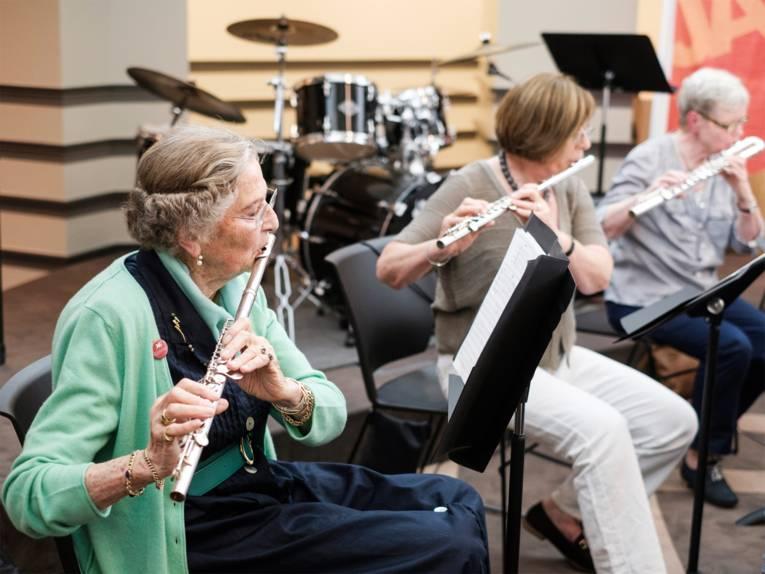 Drei Damen mit Querflöte spielen im Sitzen auf einer Bühne - das Ensemble Andantino der Musikschule