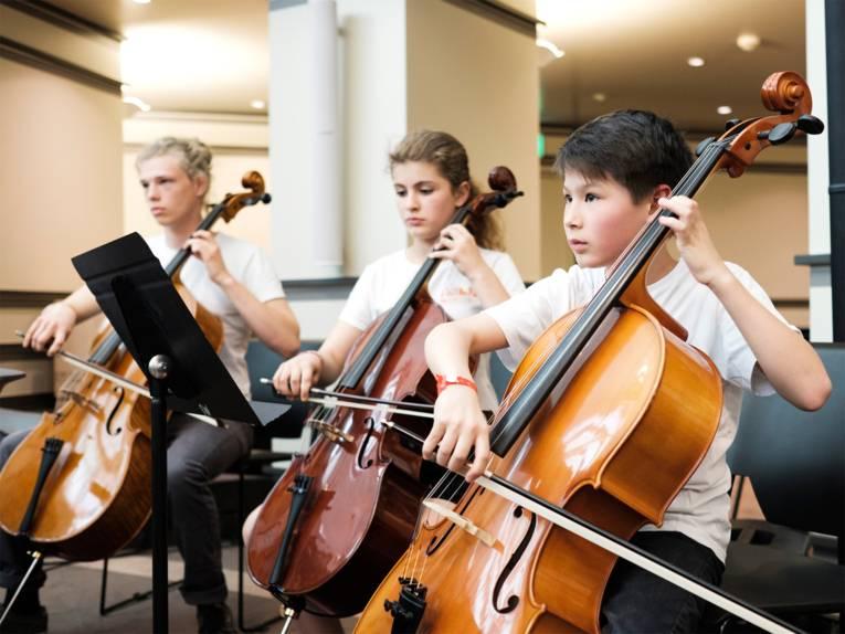 Zwei Schüler und eine Schülerin mit Streichinstrumenten (Cello/Kontrabass) spielen auf der Bühne