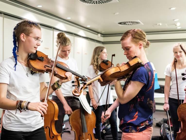 Schülerinnen der Musikschule mit Streichinstrumenten im Probenraum